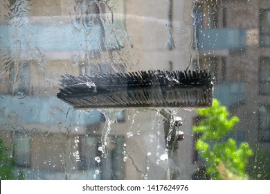 Brush. Window glass cleaning with pure water and extension pole. Washing and rinse using a reach and wash system.