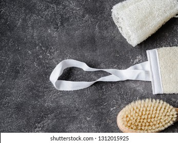 Brush with wooden body handle, loofah  wisp of bast, white terry towel and a piece of white soap on a dark background. Copy space