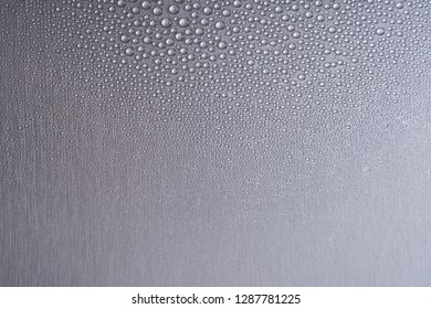 Brushed metal surface with water drops