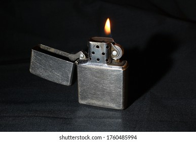 A brushed stainless steel lighter with a yellow flame, photographed on a dark background