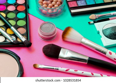 Brushes with an eyeshadow palette and lipstick in pink and mint-TONE geometric background. Decorative cosmetics for professional makeup. Eyeshadow colors trend.
