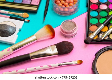 Brushes with an eyeshadow palette and lipstick in pink and turquoise geometric background. Decorative cosmetics for professional makeup. Eyeshadow colors trend.