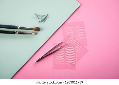 Brushes, fake lashes, tweezers and artificial eyelid crease double tapes for eye makeup on pastel rose pink and mint green background
