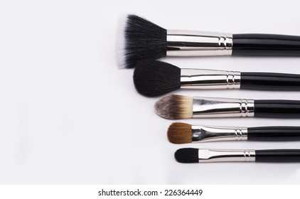 brushes for makeup lying on white background