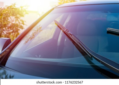 Brushes on the car glass with copy space. The work of windshield wipers - brushes and an evening sunbeam
