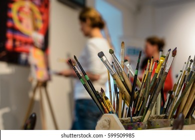 Brushes for painting. Various shapes of bristle, differents handlers of artistic tools. Unfocused background with students working in the art studio.