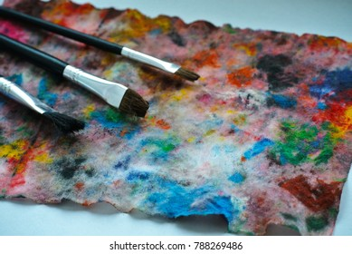 Brushes and paints on a watercolor painted on a wet napkin,Brushes on canvas