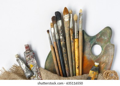 Brushes, palette and tubes with paint and a piece of canvas lie on a white background