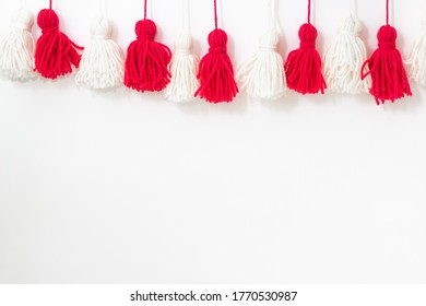 brushes from yarn of red and white color on a white background. Space for copy space. DIY yarn brushes. Garland. Garland of yarn. Pampushki from yarn. Children's creativity