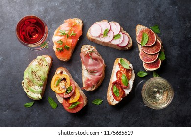 Brushetta or traditional spanish tapas. Appetizers italian antipasti snacks set on wooden board with rose and white wine. Top view and flat lay