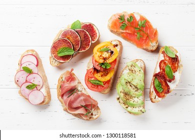 Brushetta or traditional spanish tapas. Appetizers italian antipasti snacks set on wooden board. Top view and flat lay