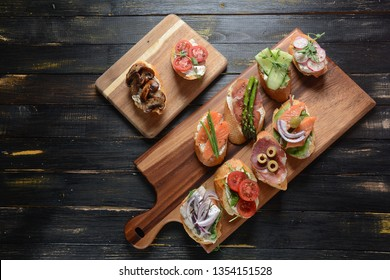 Brushetta or traditional Spanish tapas. Appetizers with Italian antipasti snacks. Variety of small sandwiches with prosciutto, cherry tomatoes, salmon, cream cheese, cucumber, radish, asparagus