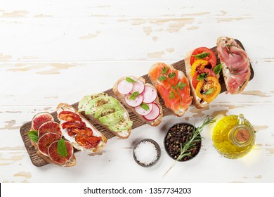 Brushetta or traditional spanish tapas. Appetizers italian antipasti snacks set on wooden board. Top view and flat lay with space for your text