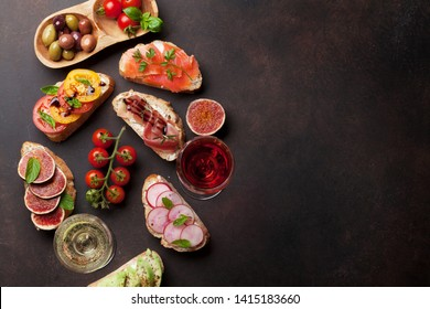 Brushetta or traditional spanish tapas. Appetizers italian antipasti snacks set with rose and white wine. Top view and flat lay with space for your text