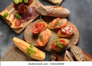 Brushetta or traditional Spanish tapas. Appetizers with Italian antipasti snacks. Variety of small sandwiches with  cherry tomatoes, salmon, cream cheese.  Prosciutto  served with melon and basil