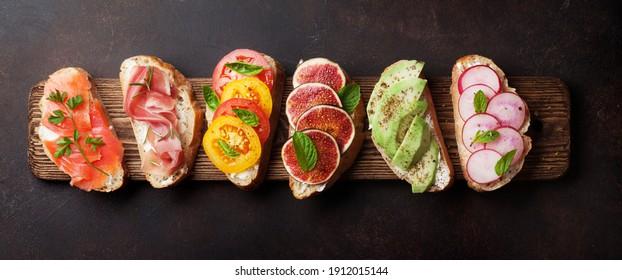 Brushetta or traditional spanish tapas. Appetizers italian antipasti snacks set on wooden board. Top view flat lay