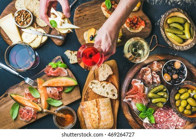 Brushettas, cheese variety, Mediterranean olives, pickles, Prosciutto di Parma with melon, salami, wine in glasses over black background, man's hands holding glass of rose and brushetta, top view