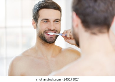 Brushing teeth in the morning. Rear view of handsome young beard man brushing his teeth and smiling while standing against a mirror