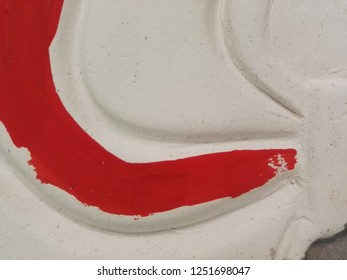 Brushstroke of red on white sculpture. Close up.