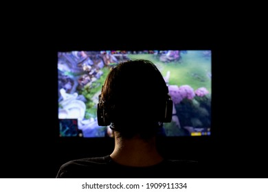 Brusque, Brazil - February 03 2021 - Dota. Young man silhouette with headphone playing video game. the new game on a screen in front of him