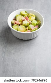 Brussel sprouts and bacon in white dish on stone background