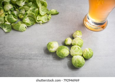 Brussel sprouts with a glass of beer on a stone background.