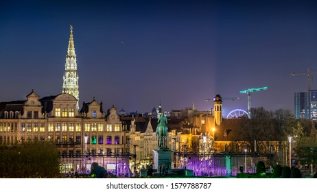 Brussels, Belgium - 04th December 2019: A photographer visiting a parc in Brussels, taking pictures from a view point of the grand place and the city hall at night with christmas lights.