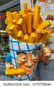 Brussels, Belgium, 10/13/2019: A model of traditional Belgian french fries on a street in the city center. Close-up. Vertical.