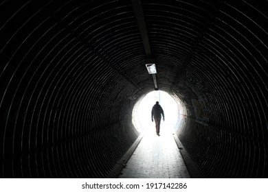 Brussels, Belgium, the 14th of February 2021. Man walking in one of the pedestrian tunnels in the city. Light at the end of the tunnel, a concept in the current corona context.