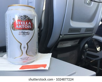 Brussels, Belgium - 15 August 2017: Aluminum can of Stella Artois on a white napkin sitting on folding seat tray in economy class during a Brussels Airlines flight.  Can of Belgium beer Stella Artois.