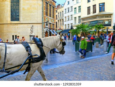 Brussels, Belgium 15.07.2016: Crowd of people in Commercial street with restaurants, bars and shops and hourse with carriage in Brussels