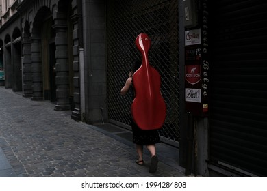 Brussels, Belgium. 17th June 2021. A woman carries a cello.