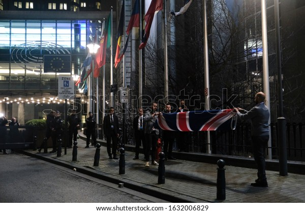 Brussels, Belgium. 31st January 2020. Staff members take down the United Kingdom's flag from outside the European Parliament building in Brussels on Brexit Day.