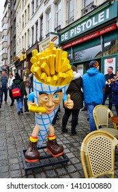 BRUSSELS, BELGIUM -9 FEB 2019- View of people eating French fries, a Belgian specialty, on the street in Brussels, Belgium.