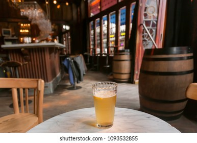 BRUSSELS, BELGIUM - APR 2: Beer with lemon for visitor of bar with vintage wooden furniture and stained-glass windows on April 2 2018. More than 1,200,000 people lives in Brussels