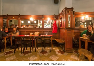 BRUSSELS, BELGIUM - APR 2: Funny people drinking and eating inside the old elegant retro cafe or bar with mirrors and wooden furniture on April 2, 2018. More than 1,200,000 people lives in Brussels