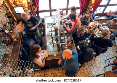 BRUSSELS, BELGIUM - APR 2: Many people drinking beer and eating dinner in small bar with tab counter and old furniture on April 2, 2018. More than 1,200,000 people lives in Brussels