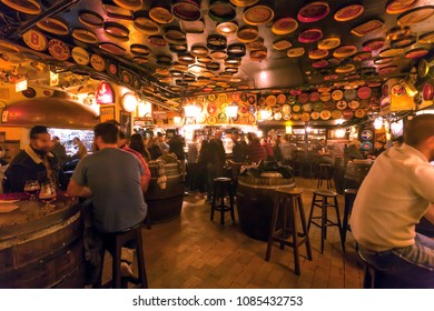 BRUSSELS, BELGIUM - APR 2: Many drinking people inside the old bar Delirium with retro furniture and wooden beer barrels on April 2, 2018. More than 1,200,000 people lives in Brussels