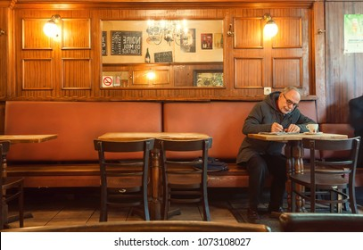 BRUSSELS, BELGIUM - APR 2: Older man alone writing letter inside old bar of cafe with historical interior and evening light on April 2, 2018. More than 1,200,000 people lives in Brussels