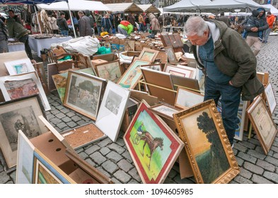 BRUSSELS, BELGIUM - APR 3: Buyer of paintings on flea market with old bargains, antique stuff, vintage decor and retro furniture on April 3 2018. More than 1,200,000 people lives in Brussels