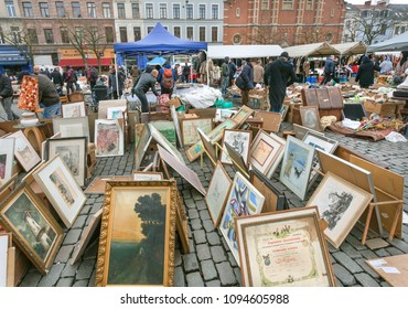 BRUSSELS, BELGIUM - APR 3: Many paintings for sale on outdoor flea market with old bargains, antique stuff, vintage decor, retro furniture on April 3 2018. More than 1,200,000 people lives in Brussels