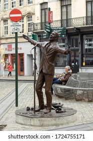 Brussels, Belgium - April 12, 2018: Jacques Brel Statue. Jacques Brel was a famous belgian singer, poet, actor. Bronze statue represent singing man behind microphone with wide open arms