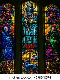BRUSSELS, BELGIUM - APRIL 18, 2009: Stained Glass in Koekelberg Basilica, Brussels, depicting God, the Holy Spirit, Jesus personified by the Agnus Dei, Joseph and Mary.