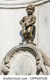 Brussels, Belgium - April 19, 2019: Manneken Pis is a historic fountain in the old town made of a bronze statue by Jerome Duquesnoy the Elder, depicting a naked little boy standing and urinating.