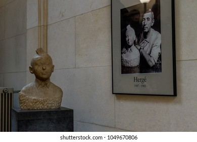 Brussels, Belgium - April 2017: A bust of cartoon character Tintin along with a photo of his creator Herge in Brussels, Belgium on a bright day