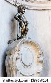 Brussels, Belgium - April 21, 2019: Manneken Pis is a historic fountain in the old town made of a bronze statue by Jerome Duquesnoy the Elder, depicting a naked little boy standing and urinating.