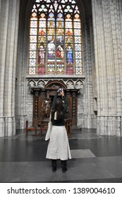 Brussels, Belgium April 29 2019: Woman Photographing Stained Glass Window in Cathedral of St. Michael and St. Gudula