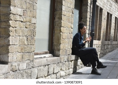 Brussels, Belgium - April 29 2019: Sitting adn Smoking Woman in the Street