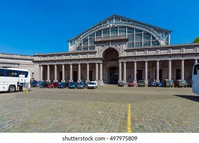 BRUSSELS, BELGIUM - APRIL 5, 2008: Tourists walk in front of Entrance to the Palais Mondial (South Hall), housing AutoWorld vintage car museum in Cinquantenaire Park