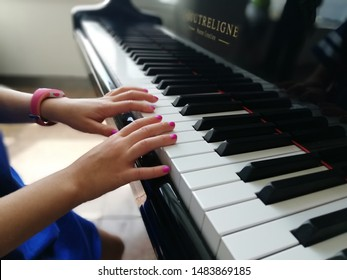 Brussels / Belgium August 10 2019 A little girl playing the grand piano close up of her hands and  keys